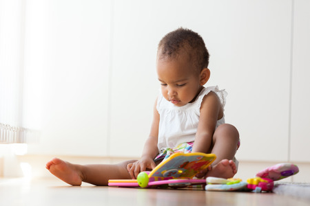 Photo pour Portrait of little African American little girl sitting on the floor and playing  - Black people - image libre de droit