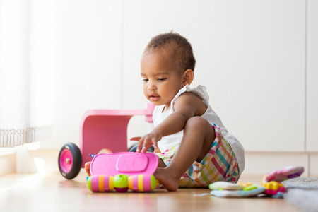 Photo for Portrait of little African American little girl sitting on the floor and playing  - Black people - Royalty Free Image