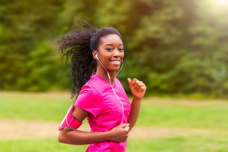 Foto de African american woman runner jogging outdoors - Fitness, people and healthy lifestyle - Imagen libre de derechos