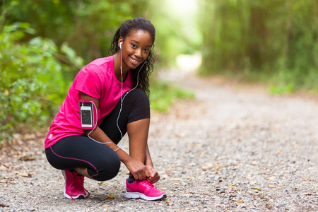 Foto de African american woman runner tightening shoe lace - Fitness, people and healthy lifestyle - Imagen libre de derechos