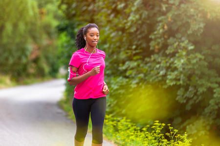 Photo pour African american woman runner jogging outdoors - Fitness, people and healthy lifestyle - image libre de droit