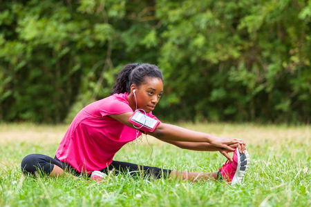 Foto de African american woman jogger stretching  - Fitness, people and healthy lifestyle - Imagen libre de derechos