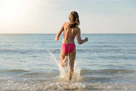 Foto de Little pretty girl running to the sea, jumping in the water. Sunny beach in the nord sea. - Imagen libre de derechos