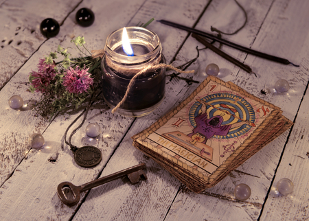 Photo for Black candle and old tarot cards on wooden planks. Halloween and fortune telling concept. Mystic background with occult and magic objects on witch table - Royalty Free Image