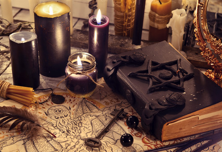 Photo pour Black magic book with black candles and demon paper. Halloween concept. Mystic background with occult and magic objects on witch table - image libre de droit