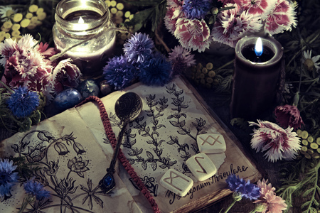 Foto de Still life with old book with botanical drawing, black candle and flowers in mystic light. Mystic background with ritual esoteric objects, occult, fortune telling and halloween concept - Imagen libre de derechos