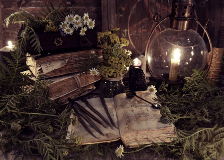 Foto de Old books, antique lamp, black candles and witch herbs. Mystic background with ritual esoteric objects, occult, fortune telling and halloween concept - Imagen libre de derechos