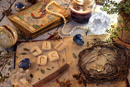 Foto de Open diary book with runes, dried herbs and tarot cards on table. Magic gothic ritual. Wicca, esoteric and occult background with vintage objects - Imagen libre de derechos