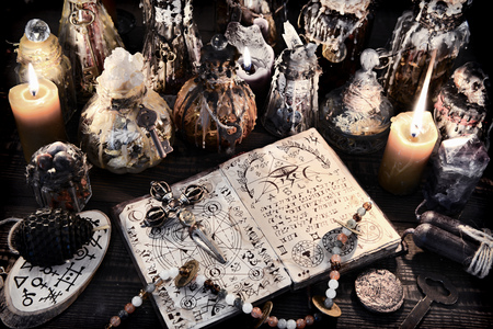 Foto de Open magic book with ancient symbols, witch bottles and black candles. Halloween, esoteric and occult background. No foreign text, all symbols on pages are fictional. - Imagen libre de derechos