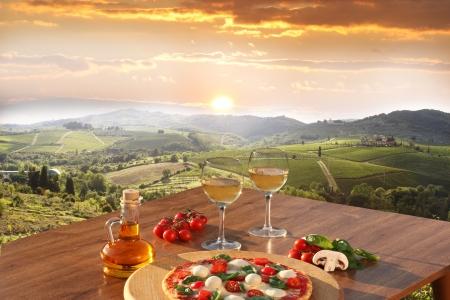 Photo pour Italian pizza and glasses of white wine in Chianti, famous vineyard landscape in Italy - image libre de droit