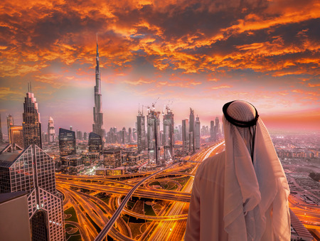 Photo for Arabian man watching cityscape of Dubai with modern futuristic architecture in United Arab Emirates. - Royalty Free Image