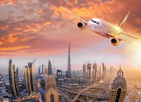 Foto de Airplane is flying over Dubai against colorful sunset in United Arab Emirates - Imagen libre de derechos