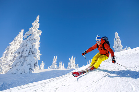 Foto de Skier skiing downhill in high mountains against blue sky - Imagen libre de derechos
