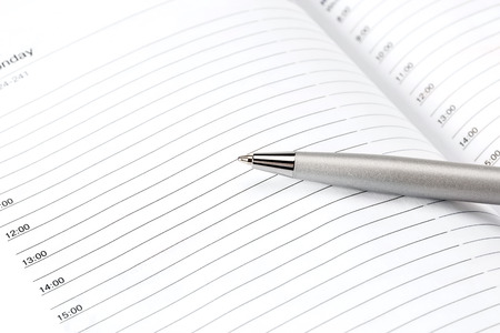 Diary with mortgaged pen on white background, isolated