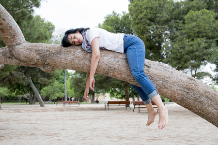 Photo for Pretty attractive woman wearing causal clothes over worked and stressed feeling relaxed sleeping in a tree in a green park.  - Royalty Free Image