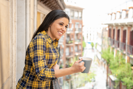 Photo pour Morning coffee. Happy beautiful latin woman smiling and drinking hot drink enjoying first cup of the day at home on outdoor balcony. Urban background. Home comfort lifestyle - image libre de droit