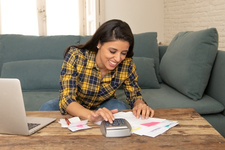 Foto de Happy attractive latin woman calculating home finances, accounting costs, charges, taxes, mortgage and paying bills at home using calculator and laptop looking cheerful and relax - Imagen libre de derechos