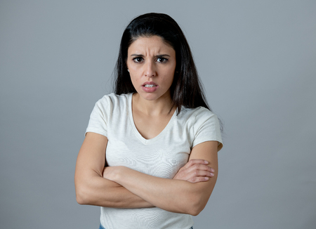 Foto de Close up portrait of an attractive young latin woman with an angry face. looking furious and moody with an intense look showing anger and rage. Human facial expressions and emotions - Imagen libre de derechos