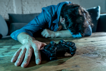 Photo for Addiction and dependency concept. close up on young mans hand with pad joystick playing video games Male addicted to console gaming concept. - Royalty Free Image