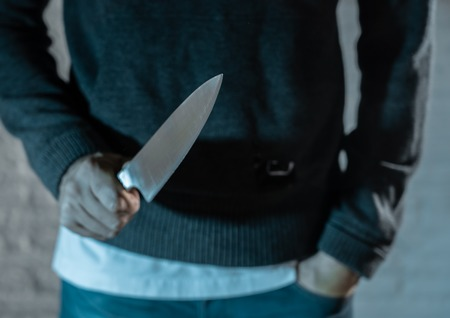 Photo for close up of a hands holding a knife of dangerous hooded man standing in the dark in London knife crime concept. - Royalty Free Image