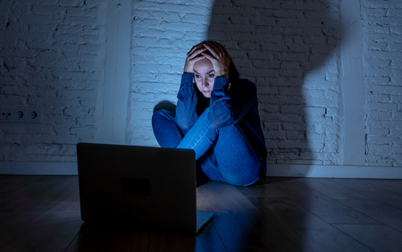 Foto de Sad and scared female Young woman with computer laptop suffering cyberbullying and harassment being online abused by stalker or gossip feeling desperate and humiliated in cyber bullying concept. - Imagen libre de derechos