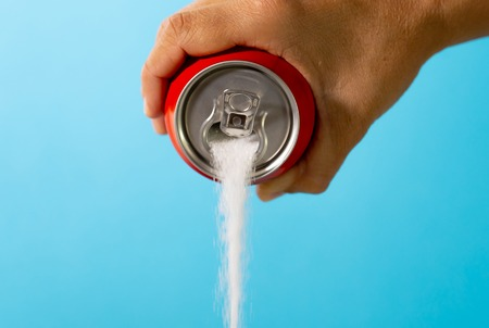 Foto de Hand holding soda can pouring crazy amount of sugar in metaphor of sugar content of refreshing drink isolated on red background in Nutrition Diet Unhealthy food Addiction and Excess calories content. - Imagen libre de derechos