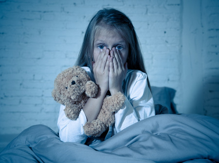 Foto de Scared little girl sitting in bed covering her face with hands holding her teddy in fear afraid of monsters in darkness in bedroom in Child nightmares imagination and psychological distress concept. - Imagen libre de derechos