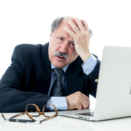 Photo pour Angry and tired mature businessman overworked at desk not understanding laptop in Older adults perception and use of technology Overtime stress and overwork concept isolated in white background - image libre de droit