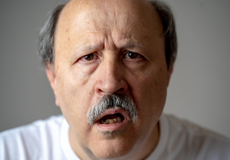 Foto de Close up portrait of senior man looking confused and lost suffering from dementia, memory loss or Alzheimer in Mental health in Older Adults and later life concept isolated on grey background. - Imagen libre de derechos