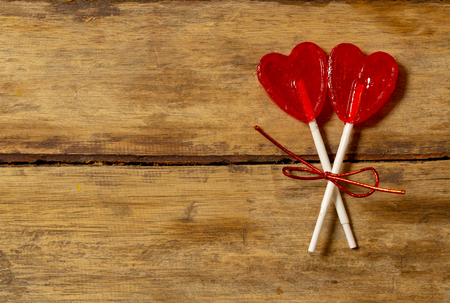 Photo pour Two cute red heart shaped lollipops on rustic wooden table and beautiful romantic mood light and blur background as metaphor of love, togetherness and Valentines day greetings car design concept. - image libre de droit