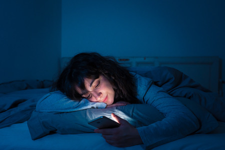 Foto de Addicted young woman chatting and surfing on the internet using her smart phone sleepy, bored and tired late at night. Dramatic dark light. In Internet, Mobile addiction and insomnia concept. - Imagen libre de derechos