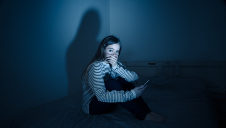 Photo for Sad desperate young teenager female girl on smart phone suffering from online bulling and harassment felling lonely and hopeless sitting on bed at night. CYberbullying and dangers of internet concept. - Royalty Free Image