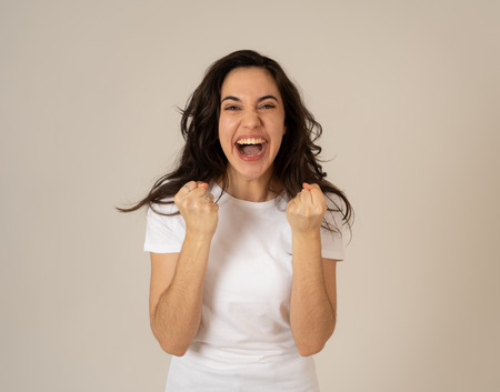 Foto de Young attractive latin woman celebrating success winning or feeling lucky and joyful dancing making celebration gestures with arms. Isolated on neutral background In People expressions and emotions. - Imagen libre de derechos