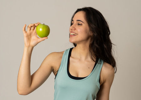 Photo pour Beautiful fitness latin young woman showing green apple feeling strong, fit and happy having fruit after exercise training In Nutrition and Fitness, Healthy lifestyle, well being and body care. - image libre de droit