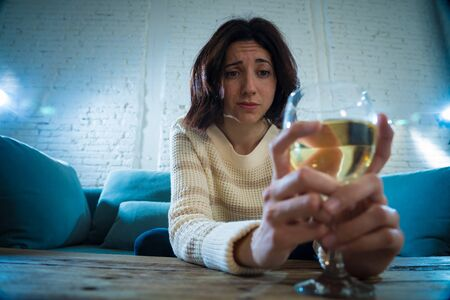 Foto de Portrait of depressed woman drinking glass of wine alone at home. Feeling distress, hopeless and frustrated, trying to feel better drinking. Unhealthy behavior, depression and alcohol concept. - Imagen libre de derechos