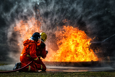Foto de firefighter training., fireman using water and extinguisher to fighting with fire flame in an emergency situation., under danger situation all firemen wearing fire fighter suit for safety. - Imagen libre de derechos