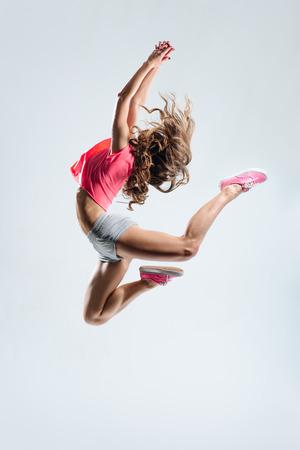 Foto de young beautiful dancer jumping on a studio background - Imagen libre de derechos