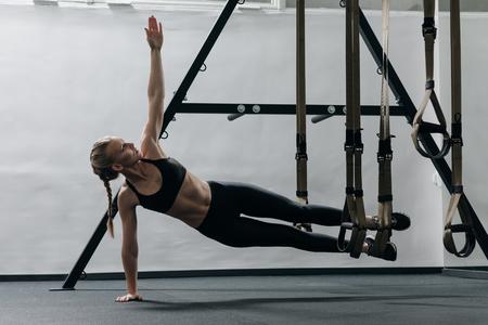 Foto de Sporty woman doing TRX exercises in the gym - Imagen libre de derechos