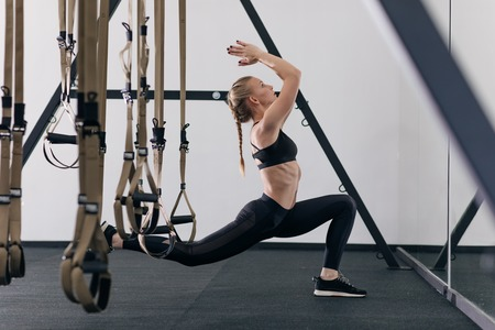 Photo for Sporty woman doing TRX exercises in the gym - Royalty Free Image
