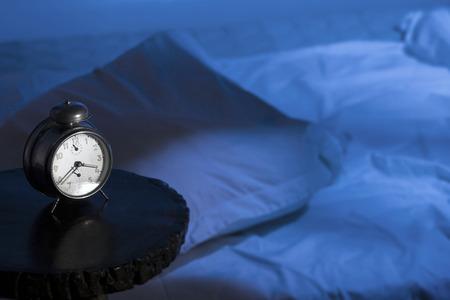 Photo pour Alarm clock with empty bed and moon-light effect. - image libre de droit