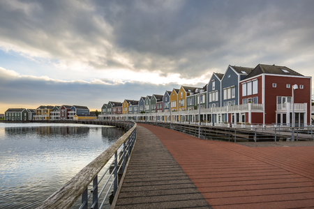 Photo pour Dutch, modern, colorful vinex architecture style houses at waterside during dramatic and clouded sunset. Houten, Utrecht. - image libre de droit