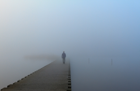 Photo for Man walking on a pier in the fog  - Royalty Free Image