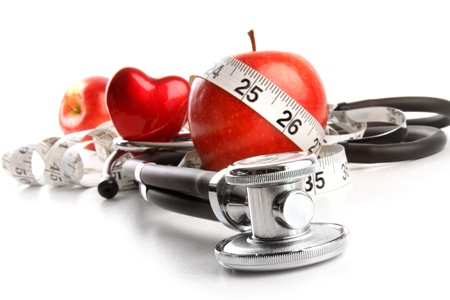 Photo for Stethoscope with red apples on a white background - Royalty Free Image