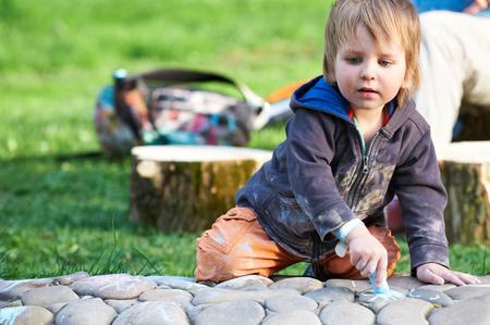 Photo pour Little boy drawing with sidewalk chalk in the park. - image libre de droit