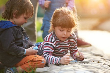 Photo pour Little boy and girl drawing with sidewalk chalk in the park - image libre de droit