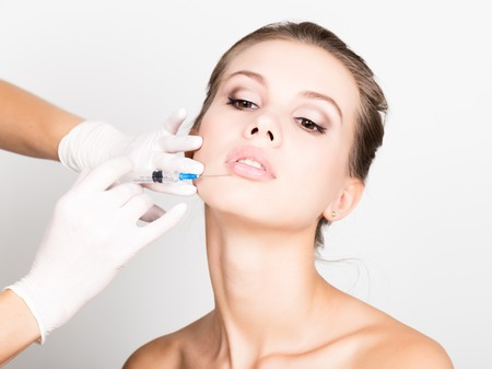 Photo pour Closeup of Beautiful young woman gets injection in eye and lips area from beautician. preservation of beauty concept. - image libre de droit