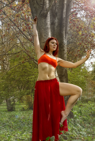 beautiful woman in red dress dancing in a autumn forest