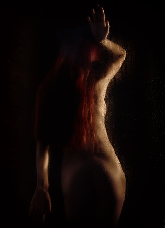 Foto de redhead naked young woman with water droplets on a body on a dark background. - Imagen libre de derechos