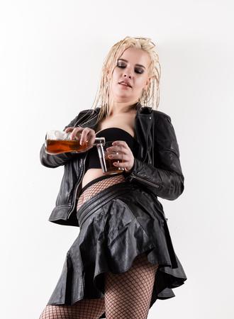 Foto de sexy woman with dreadlocks holding bottle adn glass of whiskey on a light background - Imagen libre de derechos