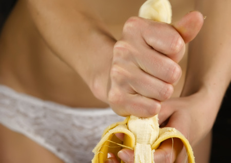Photo pour Young woman in a white panties squeezes banana in her hands. close-up buttocks and hip. - image libre de droit